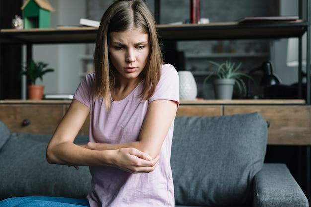 Femme malade assise sur le canapé se touchant le coude Photo gratuit