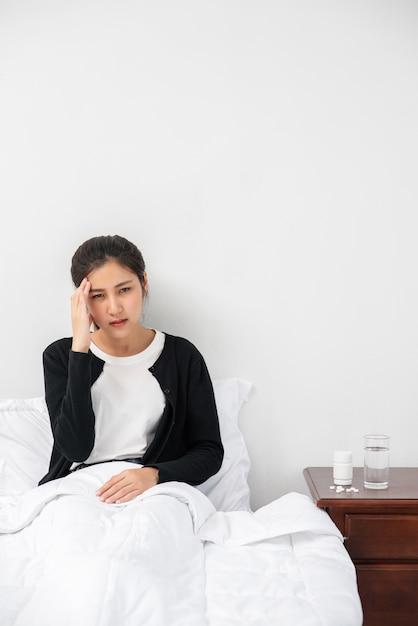 La Femme Malade Avait Mal à La Tête Et Les Mains Touchaient Sa Tête Sur Le Lit. Photo gratuit