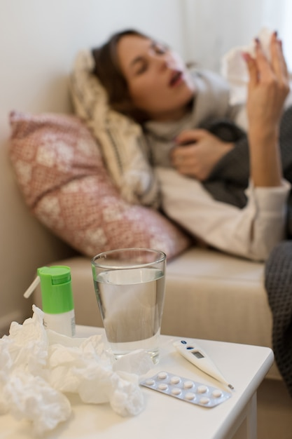 Femme Malade Floue Allongée Sur Le Canapé, éternuant Dans Un Mouchoir Photo Premium