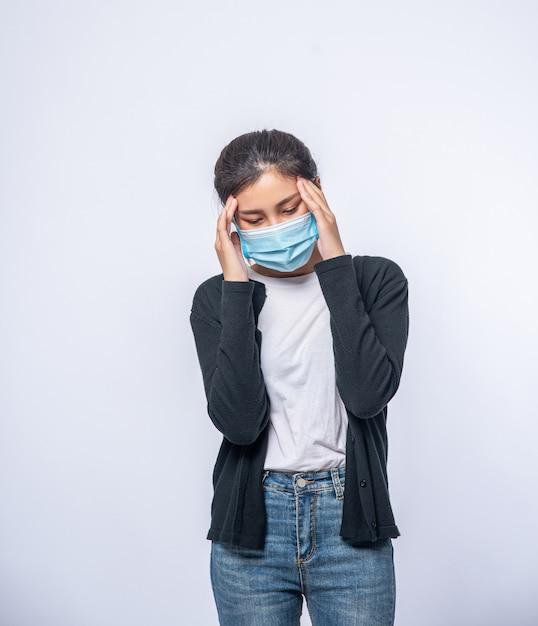 Une Femme Malade Avec Un Mal De Tête Portait Un Masque Et Posa Une Main Sur Sa Tête. Photo gratuit