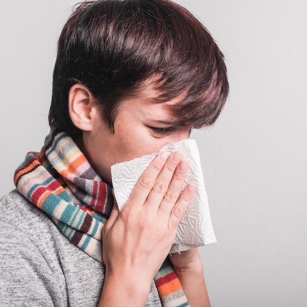 Femme malade moucher dans du papier de soie sur fond gris Photo gratuit