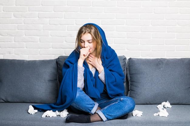 Femme Malade Avec Rhumatisme Et Maux De Tête Tenant Une Serviette, Assis Sur Un Canapé Avec Une Couverture Et Des Pilules à La Maison Photo gratuit