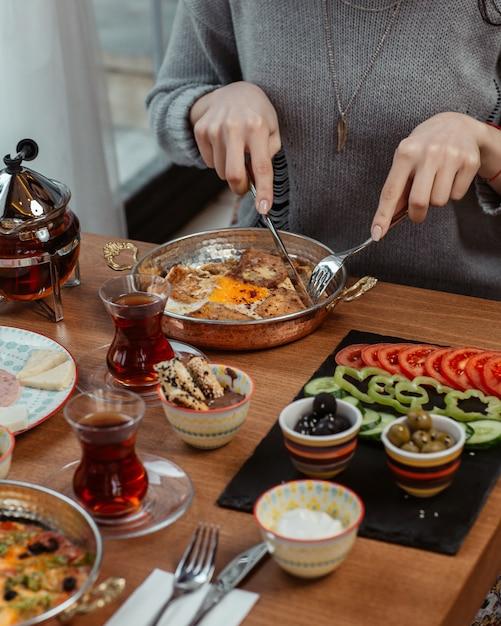 Une femme mange une omelette avec du thé noir et des aliments tout autour. Photo gratuit
