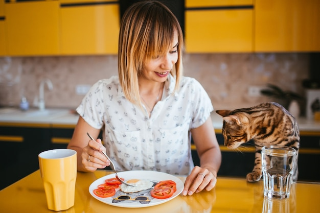 Femme mange à la table tandis que le chat bengla se tient derrière elle Photo gratuit