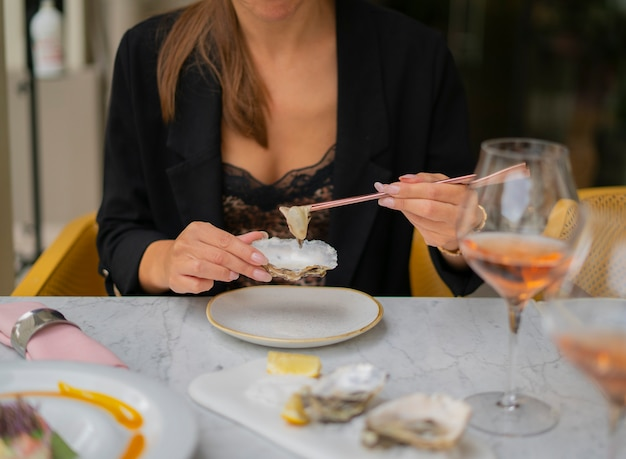 Femme Mangeant Des Huîtres Avec Des Baguettes Assis à La Table à L'extérieur Du Restaurant. Concept De Luxe Photo Premium