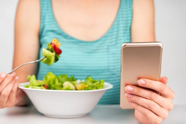 Femme mangeant une salade et regardant le téléphone Photo gratuit