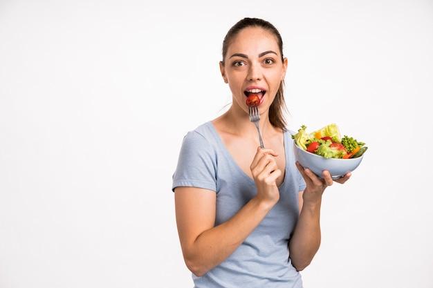 Femme mangeant une tomate avec une fourchette Photo gratuit