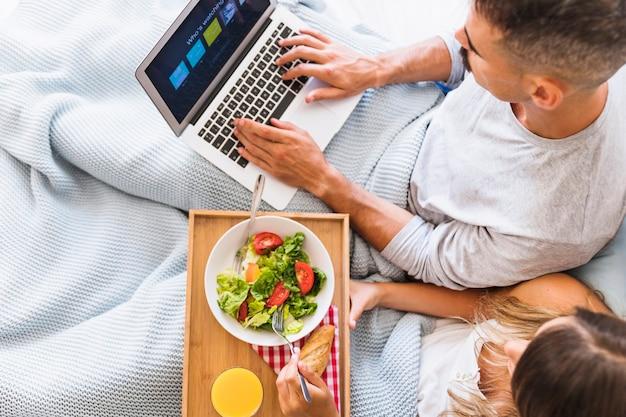 Femme, manger, salade, près, homme, choisir, compte netflix Photo gratuit