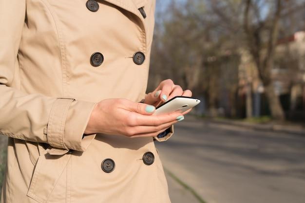 Femme En Manteau Beige Avec Une Manucure Brillante à L'aide D'un Téléphone Portable à L'extérieur Photo Premium