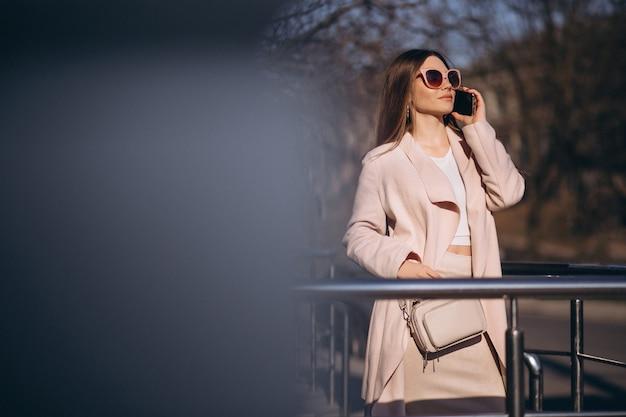 Femme en manteau marchant dans la rue et parlant au téléphone Photo gratuit