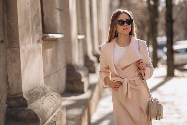 Femme en manteau marchant dans la rue Photo gratuit