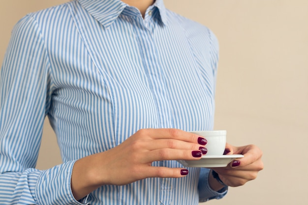 Femme avec une manucure rouge et une chemise bleue tenant une tasse de café en gros plan Photo Premium