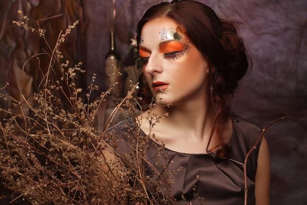 Femme Avec Un Maquillage Lumineux Avec Des Branches Sèches Photo Premium