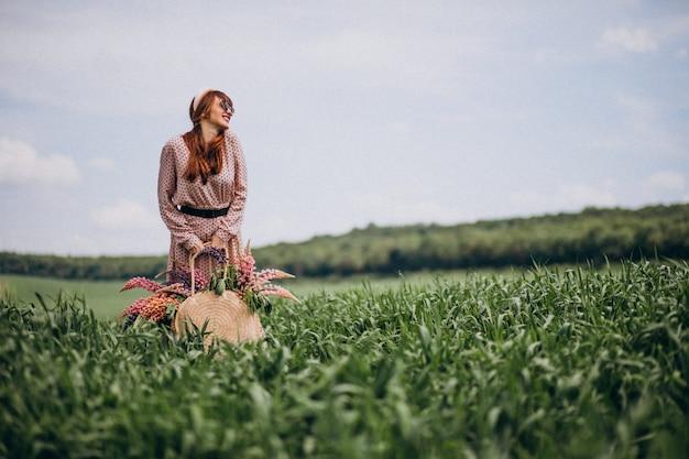Femme marchant dans un champ avec des lupinus Photo gratuit