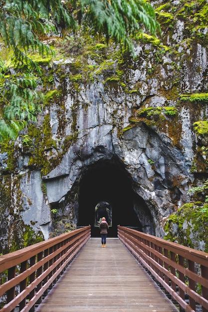 Femme Marchant à L'intérieur D'un Tunnel Naturel à Travers Un Pont Photo gratuit