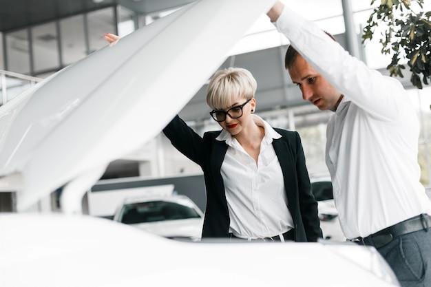 Femme et mari choisissent une voiture chez un concessionnaire et regardent sous le capot d'une voiture Photo Premium