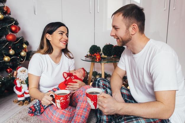 La femme et le mari gardant des tasses de café et assis sur le sol Photo gratuit