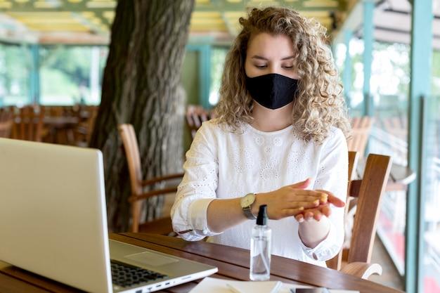 Femme Avec Masque à L'aide De Désinfectant Pour Les Mains Photo Premium