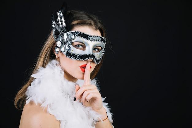 Femme avec un masque de carnaval faisant un geste de silence sur fond noir Photo gratuit