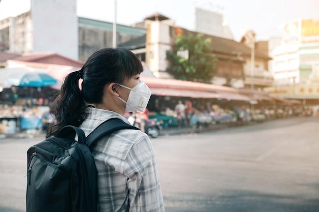 Femme avec un masque à cause de la pollution de l'air dans la ville Photo Premium