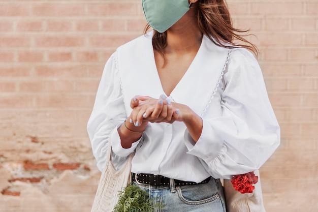Femme Avec Masque Facial à L'aide De Désinfectant Pour Les Mains Photo gratuit