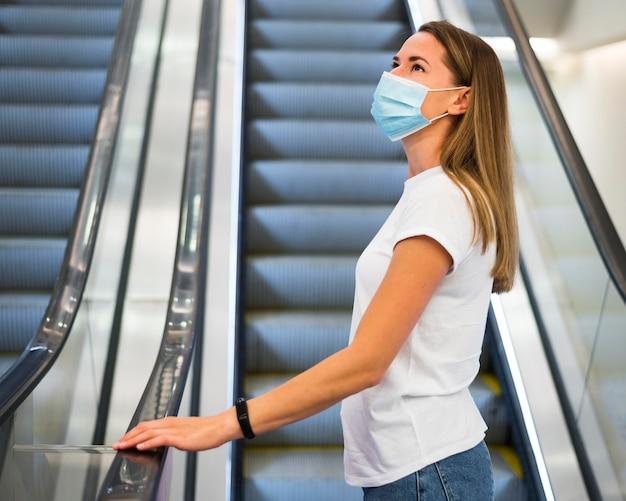 Femme Avec Masque Facial Sur L'escalator Photo gratuit