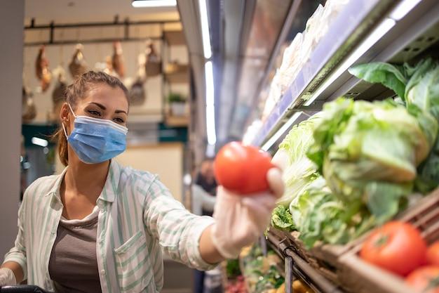 Femme Avec Masque Hygiénique Et Gants En Caoutchouc Et Panier Dans L'épicerie Acheter Des Légumes Pendant Le Virus Corona Et Se Préparer à Une Quarantaine Pandémique Photo gratuit