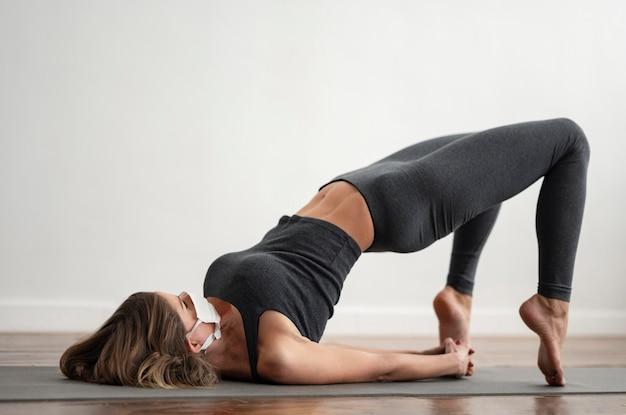 Femme Avec Masque Médical Faisant Du Yoga Sur Tapis à La Maison Photo gratuit
