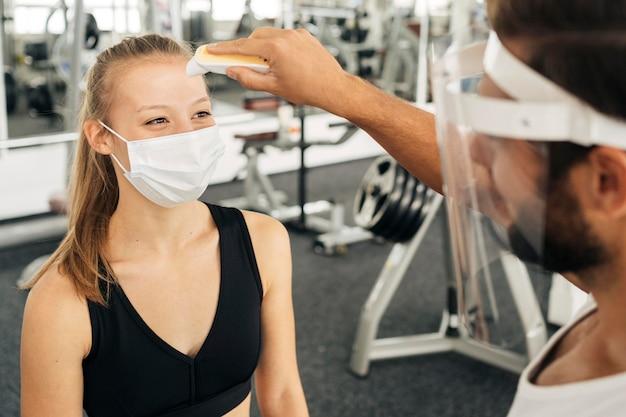 Femme Avec Masque Médical à La Salle De Sport Obtenir Sa Température Vérifiée Par Un Homme Avec Un écran Facial Photo gratuit