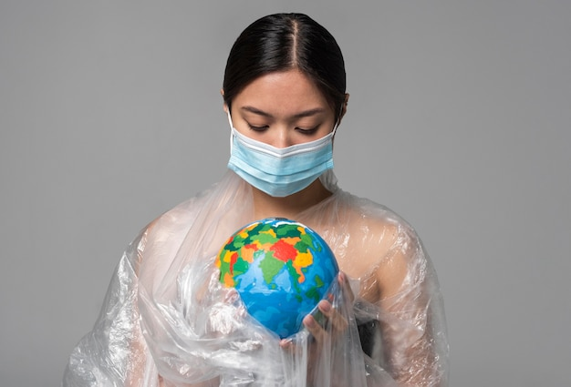 Femme Avec Masque Médical Tenant Un Globe Terrestre Tout En étant Recouvert De Plastique Photo gratuit
