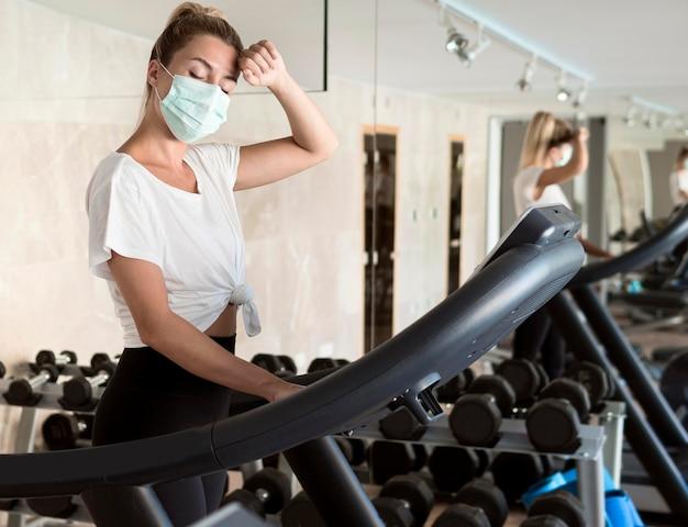 Femme Avec Masque Médical Travaillant à La Salle De Sport Photo Premium