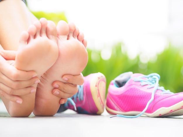Femme massant son pied douloureux en faisant de l'exercice. concept de blessures sportives en cours d'exécution. Photo Premium