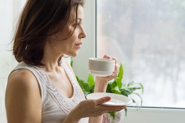 Femme mature boit le café du matin et regarde par la fenêtre Photo Premium