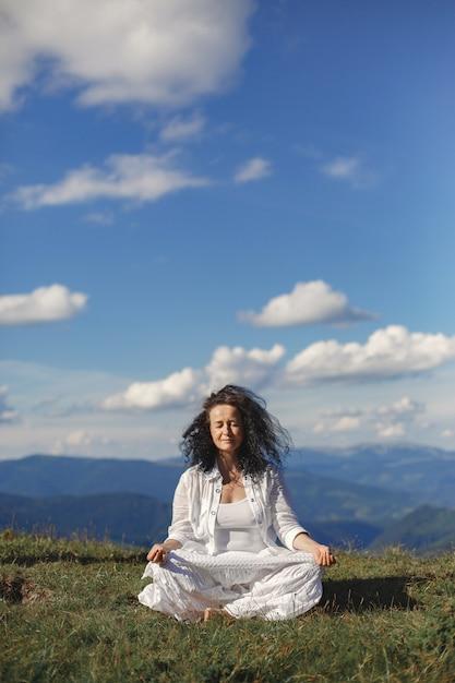 Femme Mature Fait Du Yoga. Fond De Ciel De Hauts Sommets Des Montagnes. Photo gratuit