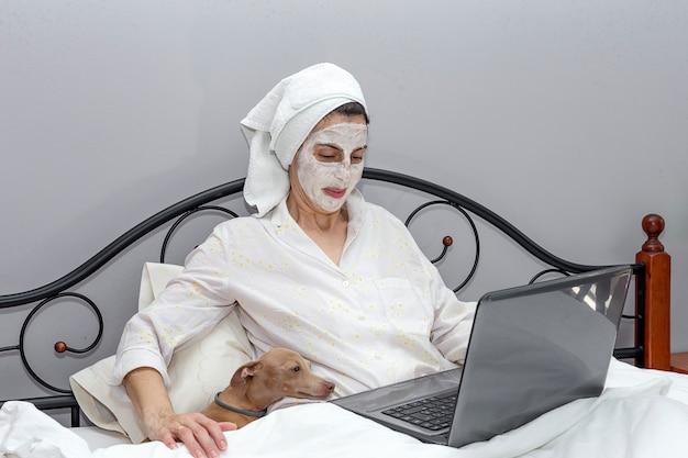 Femme Mature En Prenant Soin De Son Visage Avec Un Masque Au Lit Avec Un Chien Photo Premium