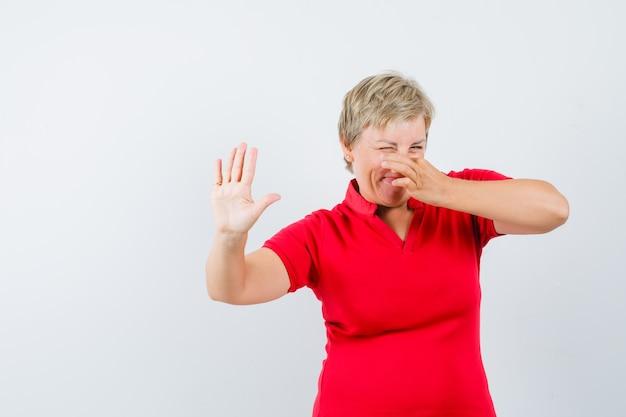 Femme Mature Se Pincer Le Nez En Raison D'une Mauvaise Odeur En T-shirt Rouge Et à La Dégoût. Photo gratuit