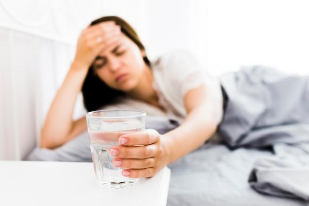Femme avec maux de tête prenant le verre d'eau Photo gratuit