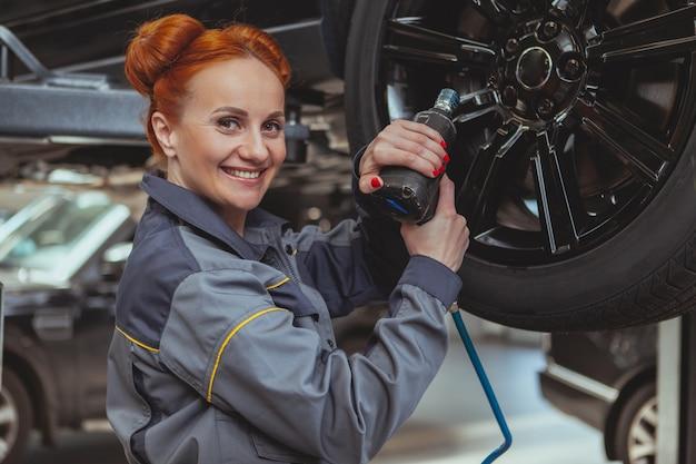 Femme mécanicien travaillant à la station service de voiture Photo Premium