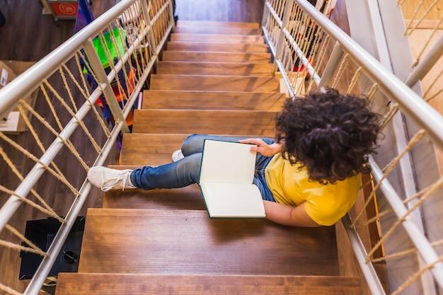 Femme méconnaissable assis dans les escaliers avec un livre Photo gratuit