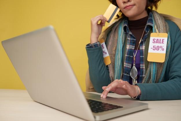 Femme méconnaissable avec carte de crédit avec ordinateur portable et écharpe avec des étiquettes de réduction Photo gratuit