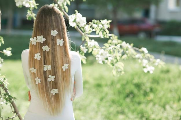 Femme Méconnaissable, Debout à L'arrière De La Caméra Avec De Longs Cheveux Blonds Avec Des Fleurs Dans Les Cheveux. Femme Sur Fond De Printemps. Dame à L'extérieur. Photo Premium