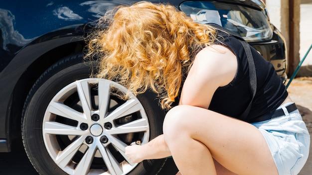 Femme méconnaissable pompage de pneu de voiture à la station d'essence Photo gratuit