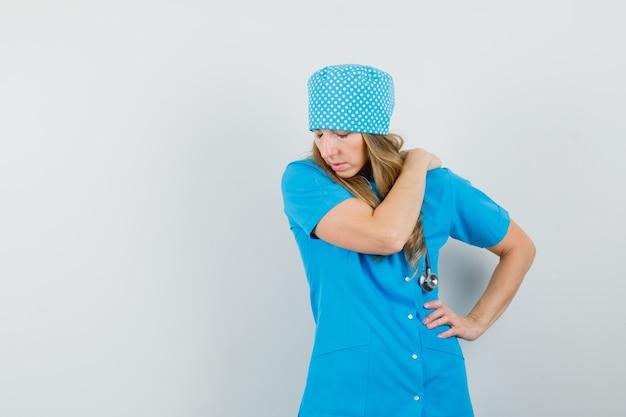 Femme Médecin Ayant Des Douleurs à L'épaule En Uniforme Bleu Et à La Recherche D'inconfort Photo gratuit