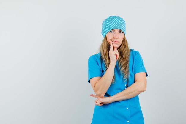 Femme Médecin Debout Dans La Pensée Pose En Uniforme Bleu Et à La Recherche D'hésitant. Photo gratuit