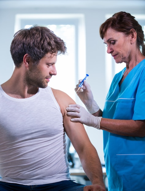 Femme médecin donnant une injection à un patient Photo gratuit