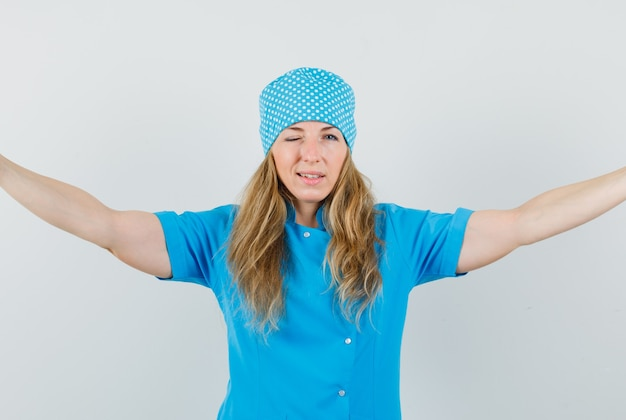 Femme Médecin écartant Les Bras Et Clignant Des Yeux En Uniforme Bleu Photo gratuit