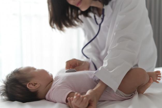 Femme médecin écoute le rythme cardiaque du nouveau-né mignon sur le lit en utilisant un stéthoscope. Photo Premium