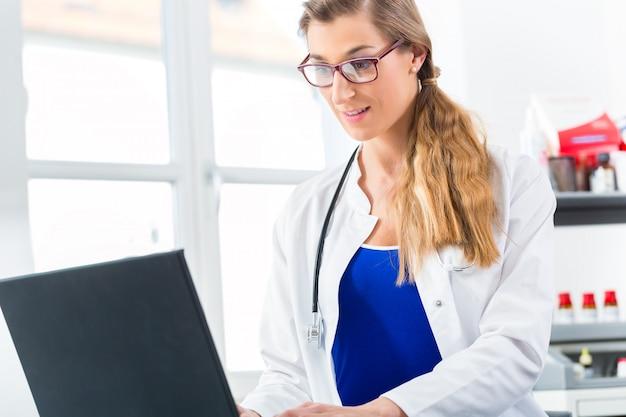 Femme médecin écrit sur pc dans sa clinique Photo Premium