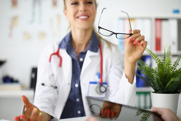 Femme Médecin Est Assise à Table En Souriant Et Tenant Des Lunettes Dans Ses Mains Photo Premium