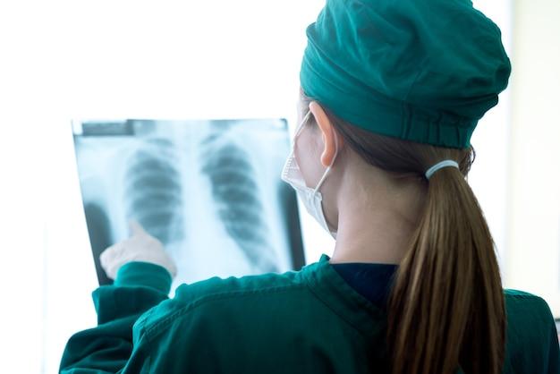 Femme médecin examinant les rayons x dans un hôpital Photo Premium